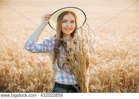 Portrait Of A Female Farmer With Hat Looking At Camera And Smiling. Caucasian Woman In Yellow Wheat