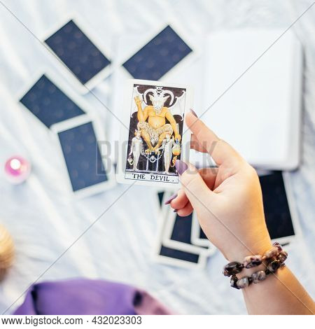Female Hand With Purple Nails Holds Tarot Card Named The Devil Over White Surface With Open Notebook