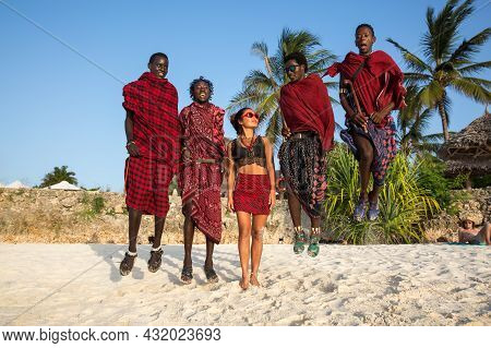 Zanzibar, Tanzania, January 27, 2021: Four Masses In Traditional Red Clothes And European Girl Jumpi