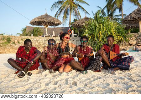 Zanzibar, Tanzania, January 27, 2021: Four Masses In Traditional Red Clothes And A European Girl Are