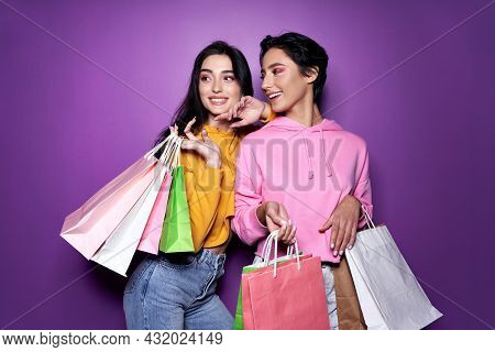 Two Happy Women Friends Shoppers Holding Shopping Bags, Female Teenage Shopaholics Standing On Purpl