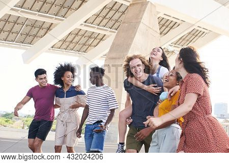 Group Of Friendly Multi-ethnic Friends Having Fun. Young Students Hugging Outside The University Or