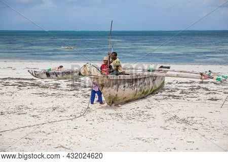 Zanzibar, Tanzania, January 22, 2021: African Children Play On An Old Fishing Catamaran Moored On A