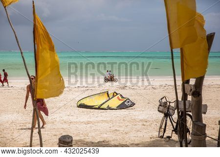 Zanzibar, Tanzania, January 22, 2021: A Couple Rides A Scooter On The Beach Against The Backdrop Of