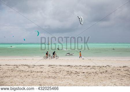 Zanzibar, Tanzania, January 22, 2021: Surfer Beach, Turquoise Sea, Leaden Stormy Sky, Many People Ri
