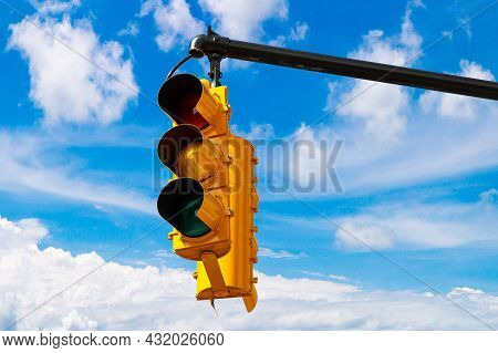 Yellow Traffic Light On Green Against Clear Blue Sky In New York City, Ny, Usa