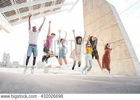 Group Of Happy Multiethnic Friends Having Fun. Young Students Jumping Outside The University.