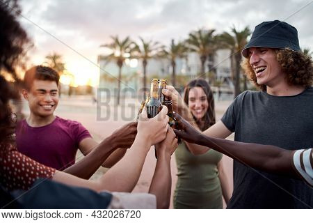A Group Of Young People With Beautiful Smiles Toasts The Sunset. Happy Mixed Race Friends Having Fun