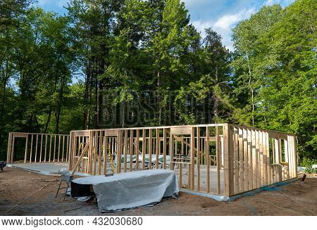New Home Construction Site With Wood Studs Of Outer Walls In Place, And Contractors Tools And Materi