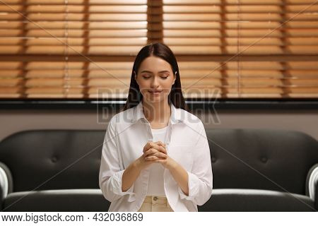 Religious Young Woman With Clasped Hands Praying Indoors