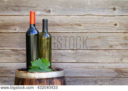 Red and white wine bottles on wine barrel on outdoor sunny garden in front of wooden wall with copy space