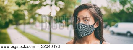 Asian woman walking outside wearing stylish fashion cloth face mask in plaid pattern. Serious young ethnic model portrait banner panorama.