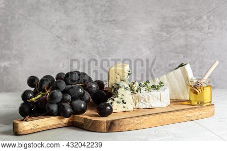 Tasting Brie, Camembert, And Roquefort On A Wooden Board. Food For Wine, Party And Romantic Dinner,