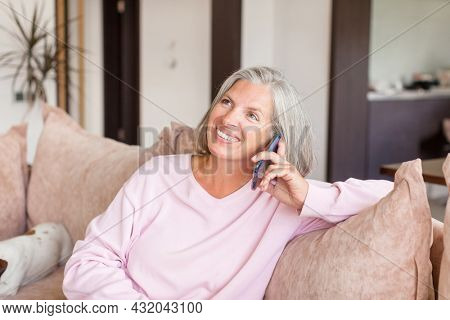 Attractive mature gray haired woman sitting on couch and calling daughter, communication. Happy Middle aged female sitting on sofa at home and talking phone