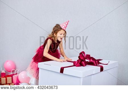 Joyful Little Girl In Pink Dress And Hat Open Big Present Gift Box With Balloons At Home Birthday Pa