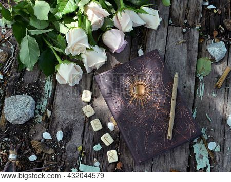 Top View Of Witch Grimoire Book, Runes And White Flowers On Planks Outside In The Garden. Esoteric,