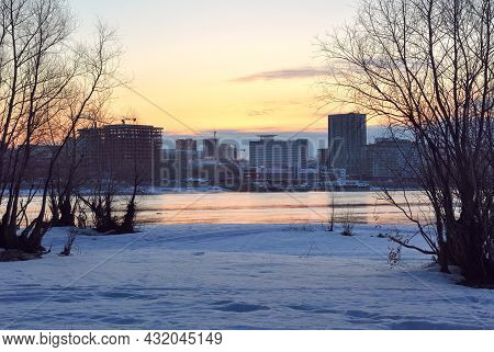 The Bank Of The Ob River At Dawn, Snow On The Bank In Spring, Bare Trees, Tall Modern Houses On The