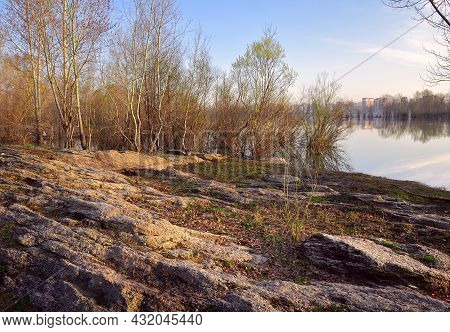 Stony Riverbank In Spring, Fresh Foliage, City Houses And Trees On The Horizon, Early Morning. Siber