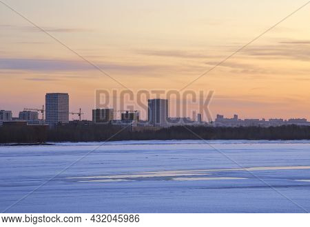 Ice And Blue Pure Snow On The Great Siberian River In Winter At Dawn. Big Houses And Cranes On The H