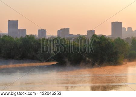Houses And Trees On The River Bank. Tall Houses, Lush Trees On The Riverbank At Dawn. Fog Over The W