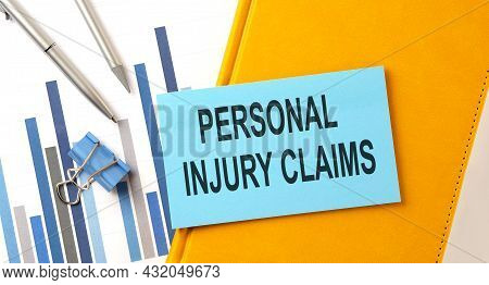 Personal Injury Claims Text On Sticker On Yellow Notebook With Chart And Pen