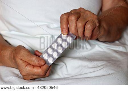 Pills In Wrinkled Hands Of Elderly Woman. Medication In Pack, Taking Sedatives, Antibiotics Or Vitam