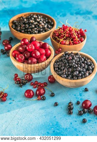 Fresh Organic Summer Berries Mix On Blue Concrete  Background. Blueberries, Red Black Currant And Ch