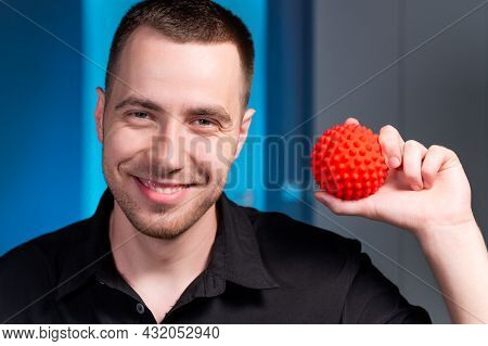Professional Young Caucasian Male Masseur In A Dark Uniform Holding A Massage Ball In His Hand For S