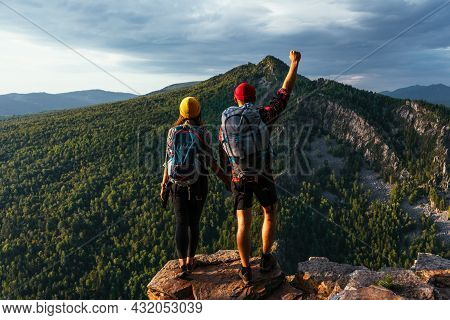 Two Happy Travelers With Backpacks On The Top Of The Mountain. Two Tourists With Backpacks Enjoy The