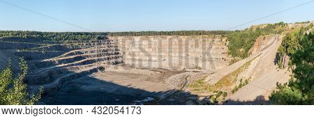 Operating Quarry For The Extraction Of Gray Granite Among The Forest, Quarry Slopes With Ledges And