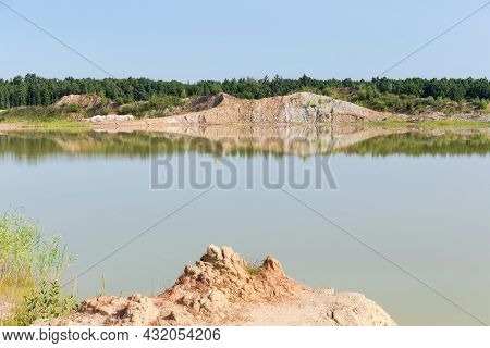 Shallow Lake On The Site Of The Abandoned Quarry Of Ilmenite Ore With Dumps On A Opposite Bank Again