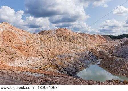 Part Of The Open Quarry For The Extraction Of Ilmenite Ore With Colored Rock Dumps Against The Sky W