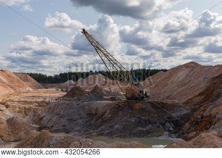 Boom Walking Excavator Digs Exposed Stratum Of Ilmenite Ore In Quarry Against The Cloudy Sky