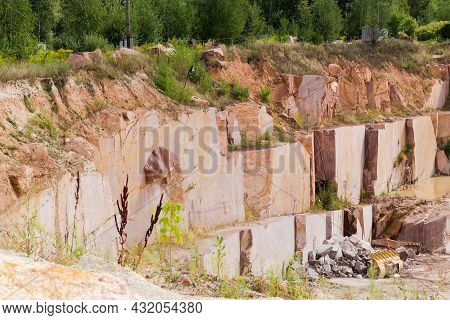 Steep Slope Of The Operating Quarry For The Extraction Of Red Granite In Summer Day
