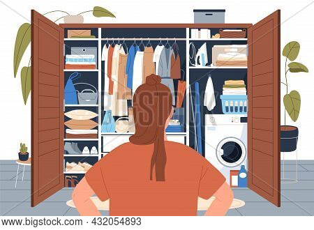 Woman Standing In Front Of Tidy Wardrobe After Decluttering. Back Of Person Looking At Open Closet W