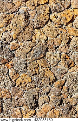 The Texture Of A Rough Wall Made Of Old Weathered Orange Shell Rock, Illuminated By Sunbeams With Ha