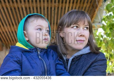 Mom And Son In Warm Autumn Clothes Looking Into Distance In One Direction. Lifestyle, Mothers Tender