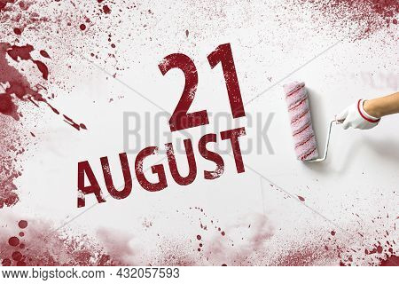 August 21st . Day 21 Of Month, Calendar Date. The Hand Holds A Roller With Red Paint And Writes A Ca