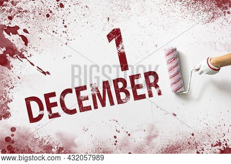 December 1st . Day 1 Of Month, Calendar Date. The Hand Holds A Roller With Red Paint And Writes A Ca
