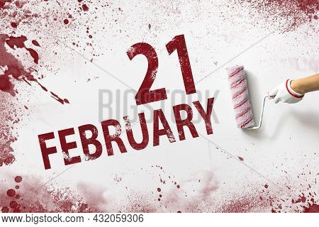 February 21st . Day 21 Of Month, Calendar Date. The Hand Holds A Roller With Red Paint And Writes A