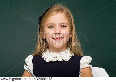 Girl Thinking While Sitting At Desk At Lesson. Beautiful Blonde Girl Elementary School Student Posin
