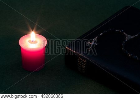 Candle With Bible And Rosary On A Green Felt Table Top