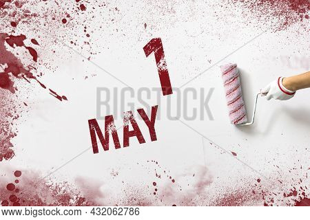 May 1st . Day 1 Of Month, Calendar Date. The Hand Holds A Roller With Red Paint And Writes A Calenda
