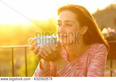 Satisfied Woman Contemplating Views Holding Coffee Mug At Sunset In A Balcony