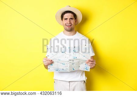 Travelling, Vacation And Tourism Concept. Puzzled Guy Tourist Cant Understand Map, Looking Confused