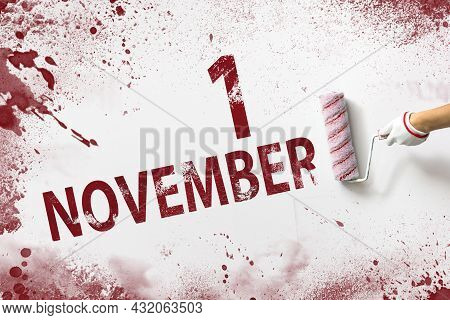 November 1st . Day 1 Of Month, Calendar Date. The Hand Holds A Roller With Red Paint And Writes A Ca
