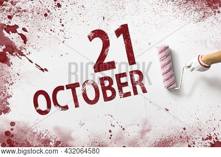 October 21st . Day 21 Of Month, Calendar Date. The Hand Holds A Roller With Red Paint And Writes A C