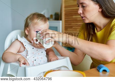 Horizontal Of Mom Giving Child Drink From Mug. Girl Drinking From Baby Bottle Sitting On High Chair.