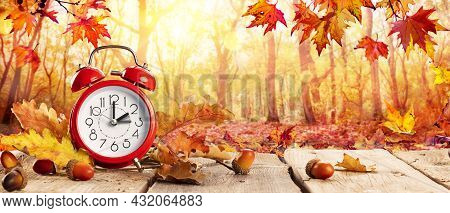 Fall Back Time - Daylight Savings End - Clock Alarm And Leaves In Autumn Background