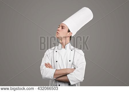 Proud Young Man In Chef Uniform Crossing Arms And Looking Away While Standing Against Gray Backgroun